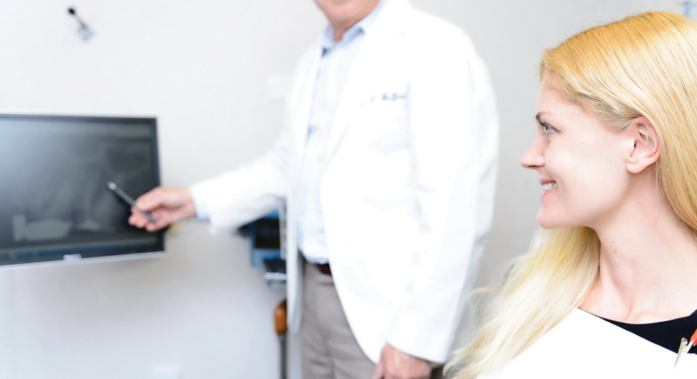 Dr. pointing at x ray on screen to patient - about endodontic associates